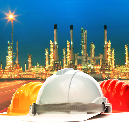savety: safety helmet against beautiful lighting of oil refinery plant in petrochemical industry estate use as industrial and safety topic background
