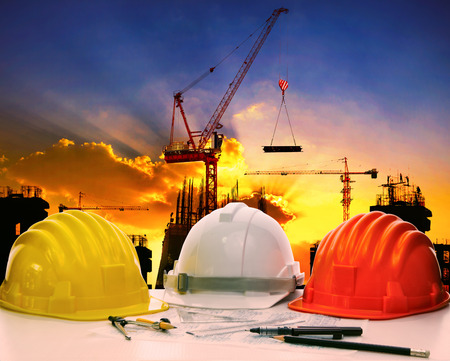 site: safety helmet on civil engineer working table against crane lifting meterial in building construction site Stock Photo