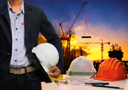 safety helmet: ingenio hombre ingeniero; h casco de seguridad blanco de pie contra la mesa de trabajo y construcci�n edificio escena