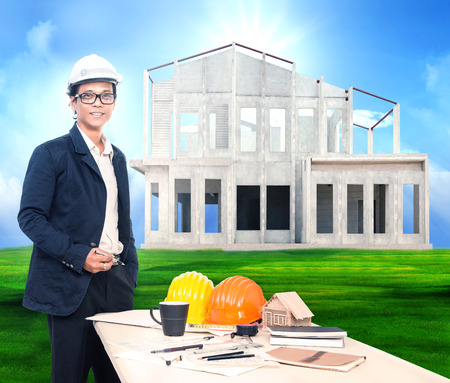 engineering man with working table and home project on beautiful green grass field background use for home ,house construction business photo