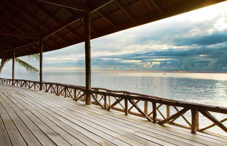 wood terrace in wooden pavillion against peaceful of heaven sea beach photo