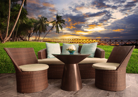 garden furniture: rattan chairs in outdoor terrace living room against beautiful sunset sky