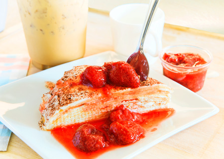 cheese crepe with sweet strawberry topping  ready to eat with cool coffee background photo