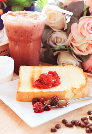 toast bread and sweet strawberry and berry jam in white dish beside cool choclolate on table top ready to eat photo