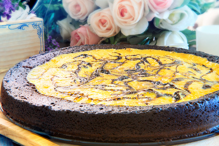 close up full big pound of brownie cheese cake on wood plate decorated with pink roses flowers bouquet on table top ready to eat photo