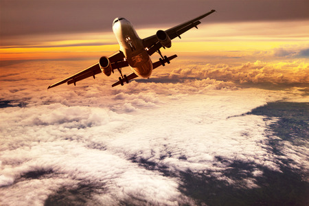 airplane take off: passenger jet plane take off to mid air against beautiful golden light of sun rising
