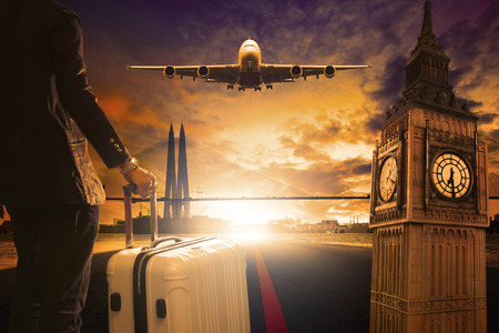 young business man standing with luggage on urban airport runway and jet plane flying above against beautiful urban scen behind Stock Photo