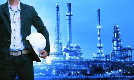 paesaggio industriale: uomo ingegneria e casco di sicurezza in piedi contro impianto di raffineria di petrolio in pesante immobiliare industria petrolchimica