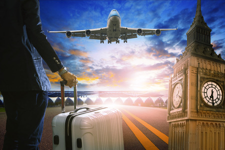 runways: business man and luggage standing in airport and passenger jet plane flying over runway against beautiful sky use for air transport and travel by airline topic