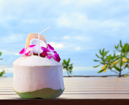 coconut drink: green coconut and orchid flowers as welcome drink in tropical destination place on top wood table against beautiful natural blue sky with copy space