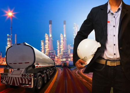 petroleum fuel: engineering man with safety helmet standing against beautiful lighting of oil refinery plant in heavy petrochemical industry and container truck transportation of petroleum Stock Photo