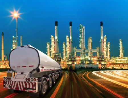 petroleum container truck and beautiful lighting of oil refinery plant in  heav petrochemicaly industry estate use for power ,energy and petroleum industrial topic Imagens