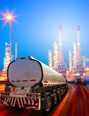 beautiful lighting of oil refinery plant in heavy petrochemical industry and container truck transportation of petroleum Stock Photo