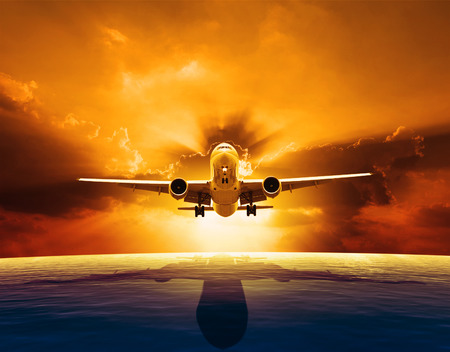 aircraft take off: passenger jet plane flying over beautiful sea level with sun set sky above