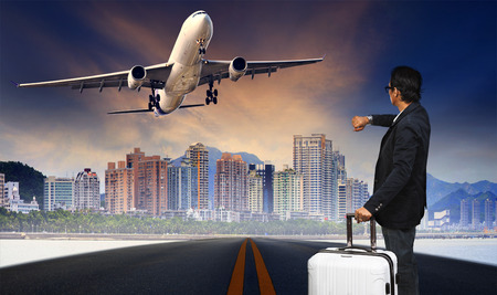 runways: man with big luggage standing on raod and watching to airplane flying over urban scene Stock Photo