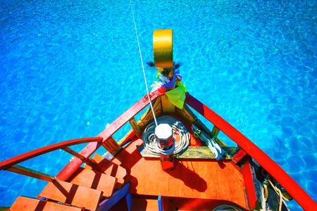 clear water: colorful of wood boat against beautiful clear blue sea water with clear water reflection Stock Photo
