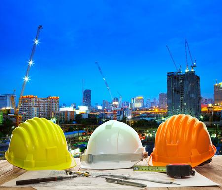 Ingenieur Arbeitstisch mit Schutzhelm und Plan schreibgerät gegen schöne Beleuchtung und städtische Gebäude Baustelle Einsatz für Land-und Stadtentwicklung backgound Standard-Bild
