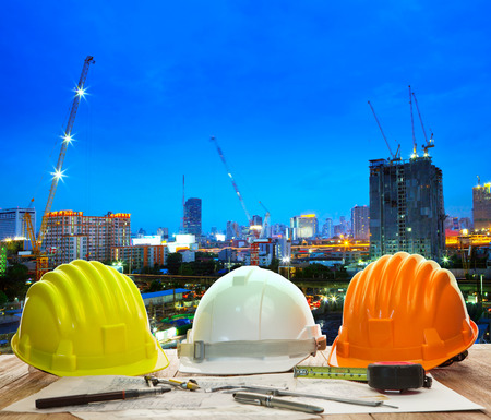 engineer working table with hard hat plan and writing tool against beautiful lighting and urban building construction site use for land and city development backgound Standard-Bild