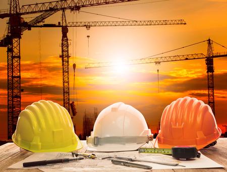 ingeniero civil: gr�a en el sitio de construcci�n y la mesa de trabajo de ingeniero civil con herramienta de escritura y el plan de construcci�n Foto de archivo