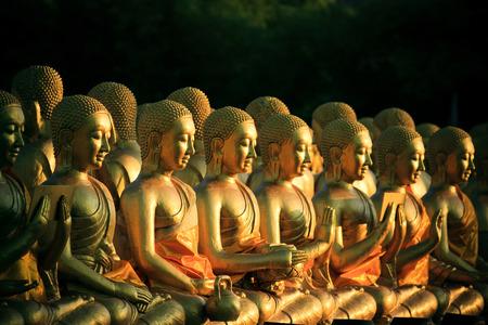 thai believe: arrangement stack of golden buddha statue in buddhism temple thailand Stock Photo