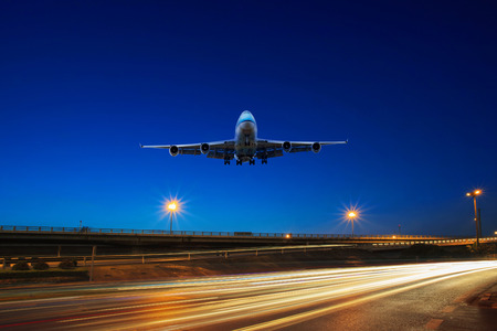 aircraft landing: flying passenger jet plane above traffic light on express ways use as transportation background