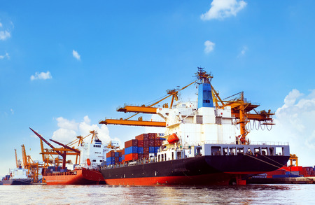 export import: container ship in port cargo dock with piers crane tool use for import export industry and freight cargo ,logistic trading shipping service business theme Editorial