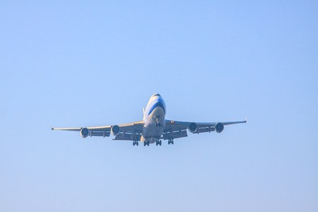 runways: passenger jet plane preparing to landing on airport runways againt blue sky background