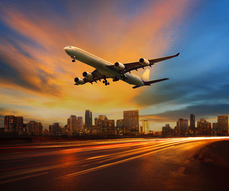 beautiful lighting of vehicle in land transportation and passenger jet plane flying above urban scene use for transport business and people traveling theme