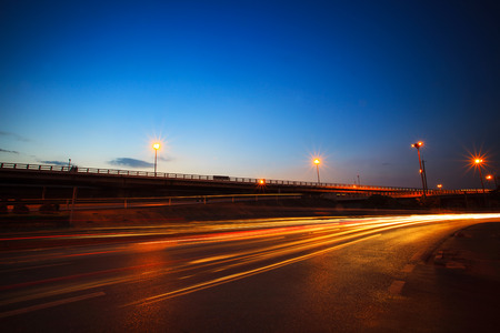 beautiful blue dusky sky peak of twilight time and light painting on asphalt road by vehicle moving use for land transport and urban life background photo