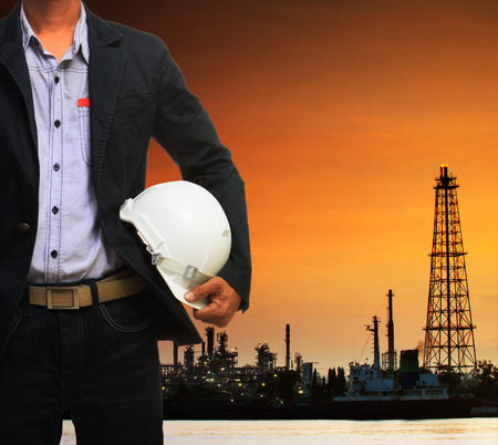 engineering man and safety helmet standing against beautiful dusky sky of oil refinery plant scene use for energy of fossil fuel and industry topic background photo