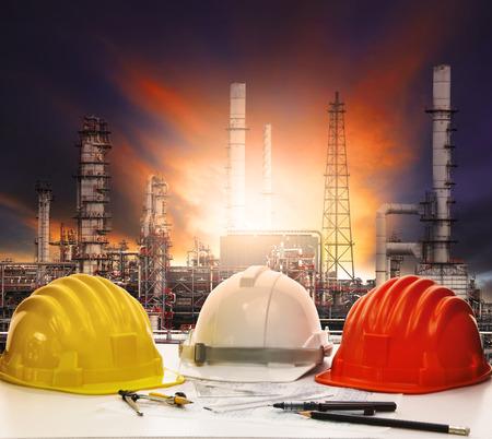 安全ヘルメットと石油製油所背景を持つエンジニア作業テーブル上の作業シート
