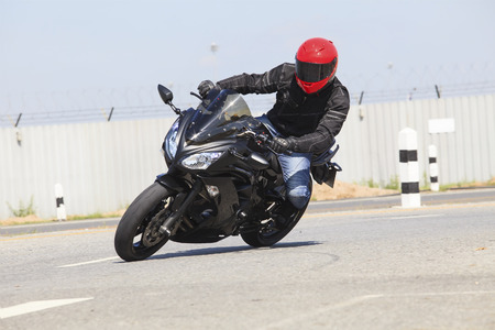 sharp curve: young man wearing safety suit and red anti knock helmet  riding big bike motorcycle running in sharp curve asphalt road use for motor sport activity of rider