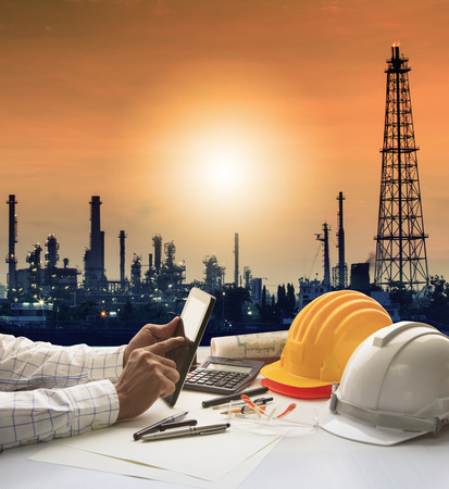 chemical engineering: engineering working on computer tablet against silhouette of oil refinery plant in heavy petrochemical industry estate