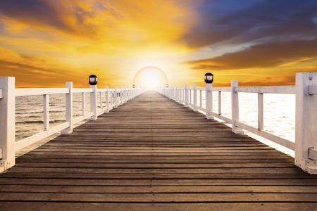 the rising sun: puesta de sol escena y muelle viejo puente de madera con nadie contra el uso hermoso cielo oscuro para el fondo natural, telón de fondo y la escena del mar de usos múltiples