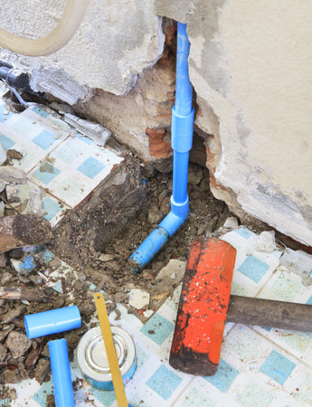 broken house: repairs of home clean water plumbing tube and heavy hammer and related tool