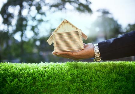 美しい緑の芝生のフィールドでビジネス男と木の家モデルの手用の住宅、住宅の不動産および土地開発