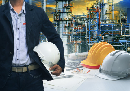 human energy: engineering man standing with white safety helmet against  oil refinery in petrochemical industry Stock Photo
