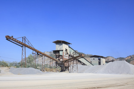 limestone: rock crusher machine industry chain moving to logistic gravel use for construction matterial and pollution of heavy industry Stock Photo