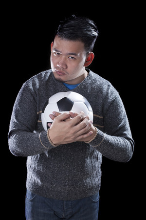objec: face of soccer lover holding football ball isolated black background use for sport and people activities theme