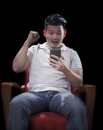 arm chairs: man sitting on arm chairs and watching to smart phone with exciting face