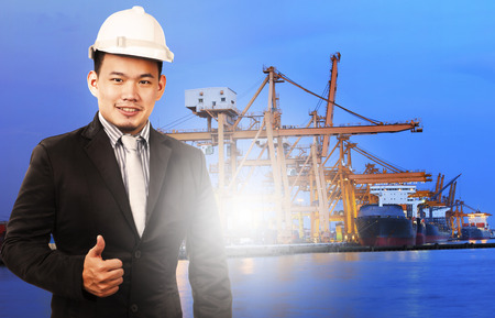 comercial: young manager man standing and sign good quality control of port shipping import export and logistic industry service against ship in comercial ship piers
