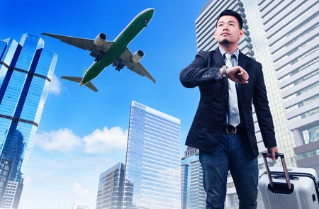 take time off: business man and big belonging luggage watching to sky and hand watch time against high building skyscrapers and passenger jet plane flying above use for aircrat and air transportation ,traveling of people theme Stock Photo