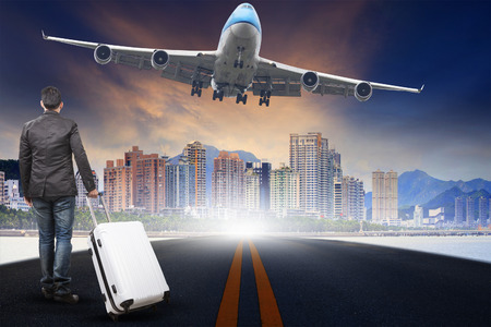 runways: young man with belonging luggage standing against urban scene and passenger jet plane flying over sky