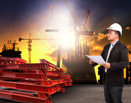 land use: engineering man working in building construction site and reading plan ducument  use for construciton industrial business and land development topic Stock Photo