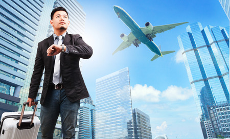 belonging: business man and belonging luggage watching to sky and hand watch against high building skyscrapers and passenger plane flying above use for aircraft ,air transportation ,traveling of people theme
