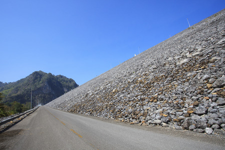infra construction: perspective of road to top of khao laem rock dam in kanchanaburi thailand Stock Photo