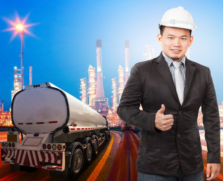 body scape: young engineering man with safety helmet standing against beautiful lighting of oil refinery plant in heavy petrochemical industry and container truck transportation of petroleum