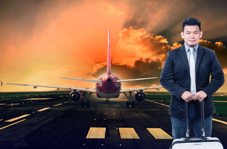 runways: young man and luggage standing against passenger jet plane preparing to take off on airport runways