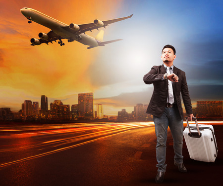 runways: young man and traveling bag luggage standing on city road looking to sky and air plane flying to airport runways use for people traveling theme