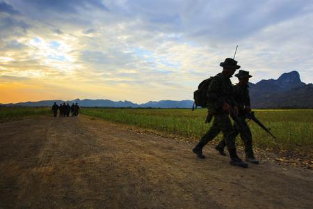 patrolling: silhouette motion of long range patrolling soldier walking on dirt road against beautiful enening sky Stock Photo